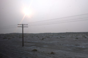 Desert landscape with one telephone pole and grey sky from wildfires.