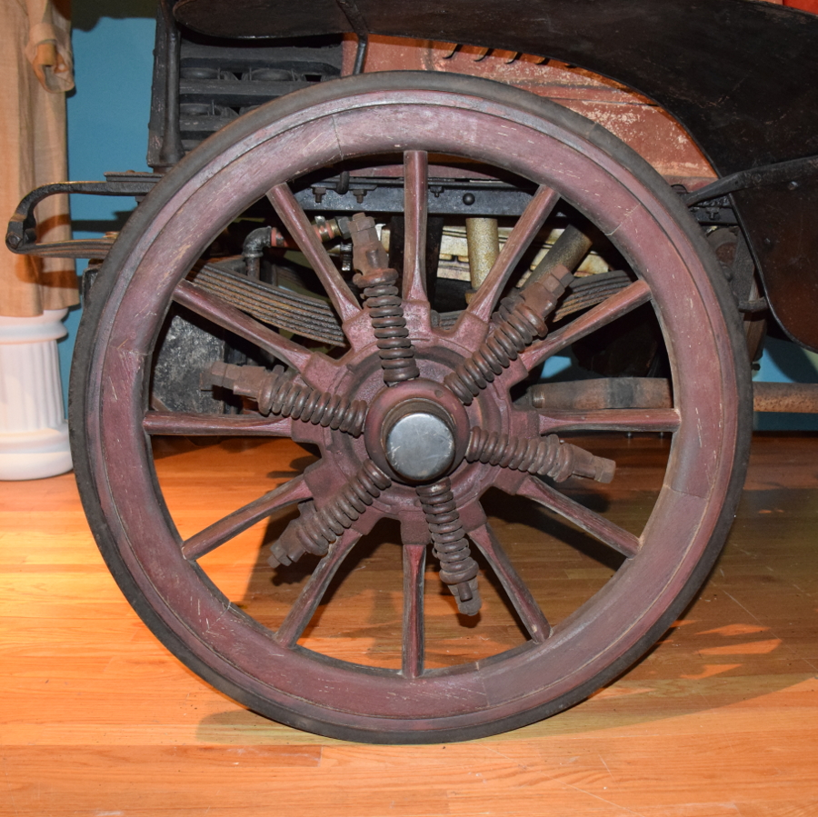 Twelve spoke wooden wheel suspended on six coil springs.