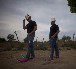 Two young Mexican men wearing cowboy hats and pink cowboy boots with 24 inch toes curving upwards.