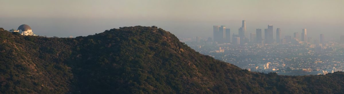 Panoramic photo of a smoggy day in LA including the Griffith Park Observatory and the downtown skyline