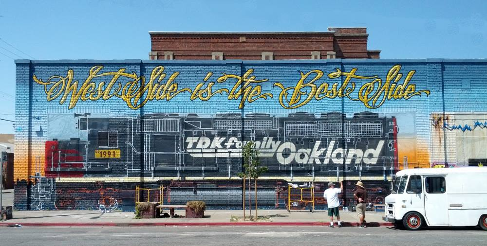 """Artist talking about the collaborative project of painting a mural around a warehouse in West Oakland, California, titled """"West Side is the Best\ Side."""""""